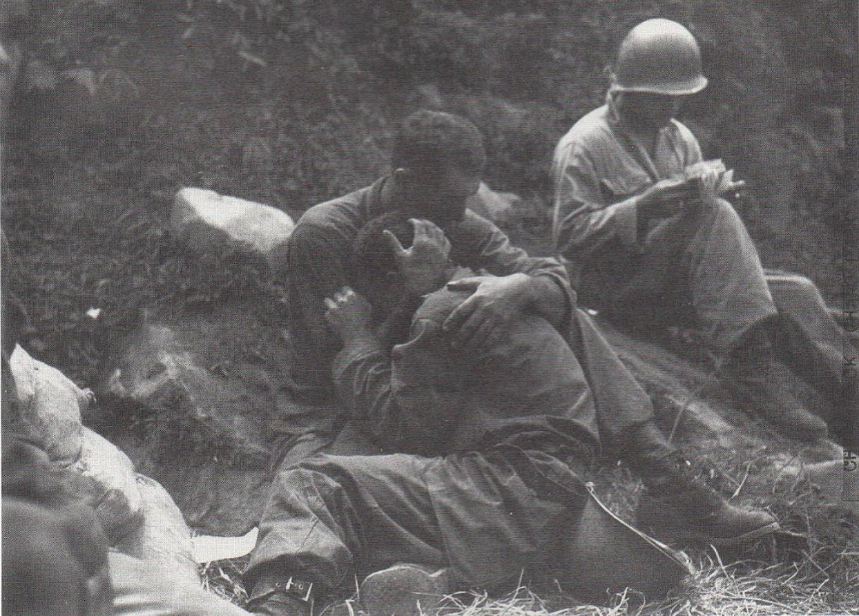 This photograph was published during the first months of the Korea war. The soldier is crying because he lost a comrade. Another one, behind him, records the losses. (photo)