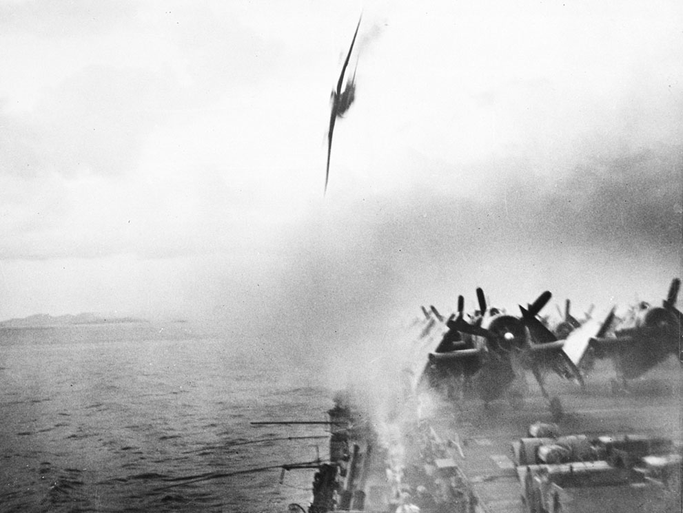 A pilot dashes towards the already hit by other kamikaze USS Sangamon, but misses and hits the waters just moments after the photo was taken – 4 May 1945 (photo)